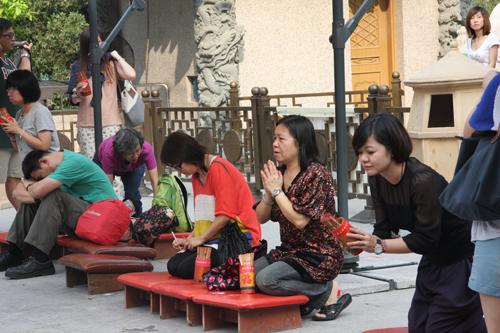 Donne con i bastonici per predire il futuro nel tempio taoista di Wong Tai Sin, a Hong Kong. Foto di Marco Restelli