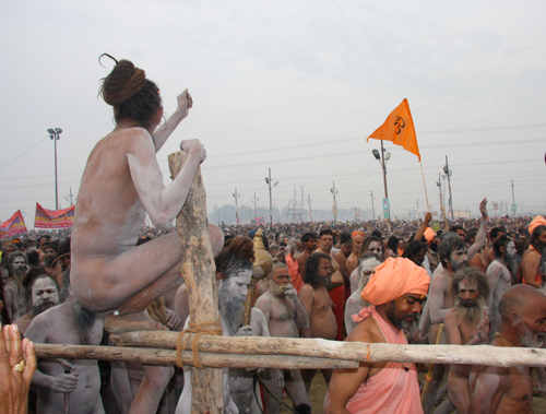 Un asceta dei Naga Baba su una staccionata incita i suoi confratelli  al Maha Kumbha Mela 2013. Foto di Marco Restelli